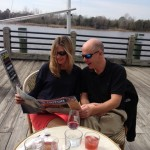 """Jamie Lynn Miller shot this photo of Capt. Jason Bell and Tracy at Port City Marina in Wilmington, North Carolina. The marina is downtown on the Cape Fear River. Miller shared this story about the couple: Capt. Jason Bell and First Mate Tracy Bell are married. The photo was taken on Tracy's birthday, March 1, at Le Catalan, a French bistro and wine bar along Wilmington's Riverwalk. Their boat is Gypsie, a ketch-rigged 52-foot Irwin. Tracy and Jason met in Grenada while Jason (a Scottish sea captain) was captaining Southern Winds, and Tracy and her father were sailing aboard Gypsie. They spent just 24 hours together before their respective ships sailed separate ways. They kept in touch via email, and two weeks later, Jason's vacation time arrived. He asked Tracy to come home with him to Scotland--this woman he'd known for 24 hours--and somehow, she convinced her dad it was a good idea.  They fell in love quickly, but after a blissful time abroad, it was time to head back to their designated courses; Jason returned to his post, Tracy rejoined her father, and neither knew what the future would bring. They tried to keep in touch, but they didn't know how, when, or if they could be together again. Two months later, in the Sir Francis Drake Channel near the British Virgin Islands, their ships literally passed in the night. Tracy grabbed the radio and called, """"Southern Winds?"""" Jason responded immediately: """"Gypsie?"""". Their ships slowed and Tracy and Jason moved their dingies toward one another, pledging their love in the middle of the ocean. Now married with three children, the Bells have made their way back to Tracy's native North Carolina, and they've since inherited Gypsie from Tracy's dad."""