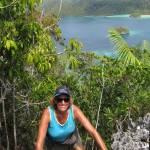 Sue Hacking climbs a forested limestone hill over Wayag Islands.PHOTObyJON HACKING