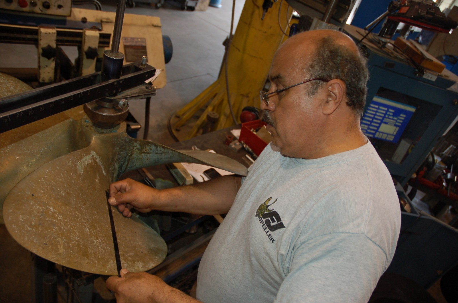 Salvador Mejia measures and marks damaged areas on a propeller at Frank & Jimmie's Propeller in Ft. Lauderdale last month. PHOTOS BY DORIE COX