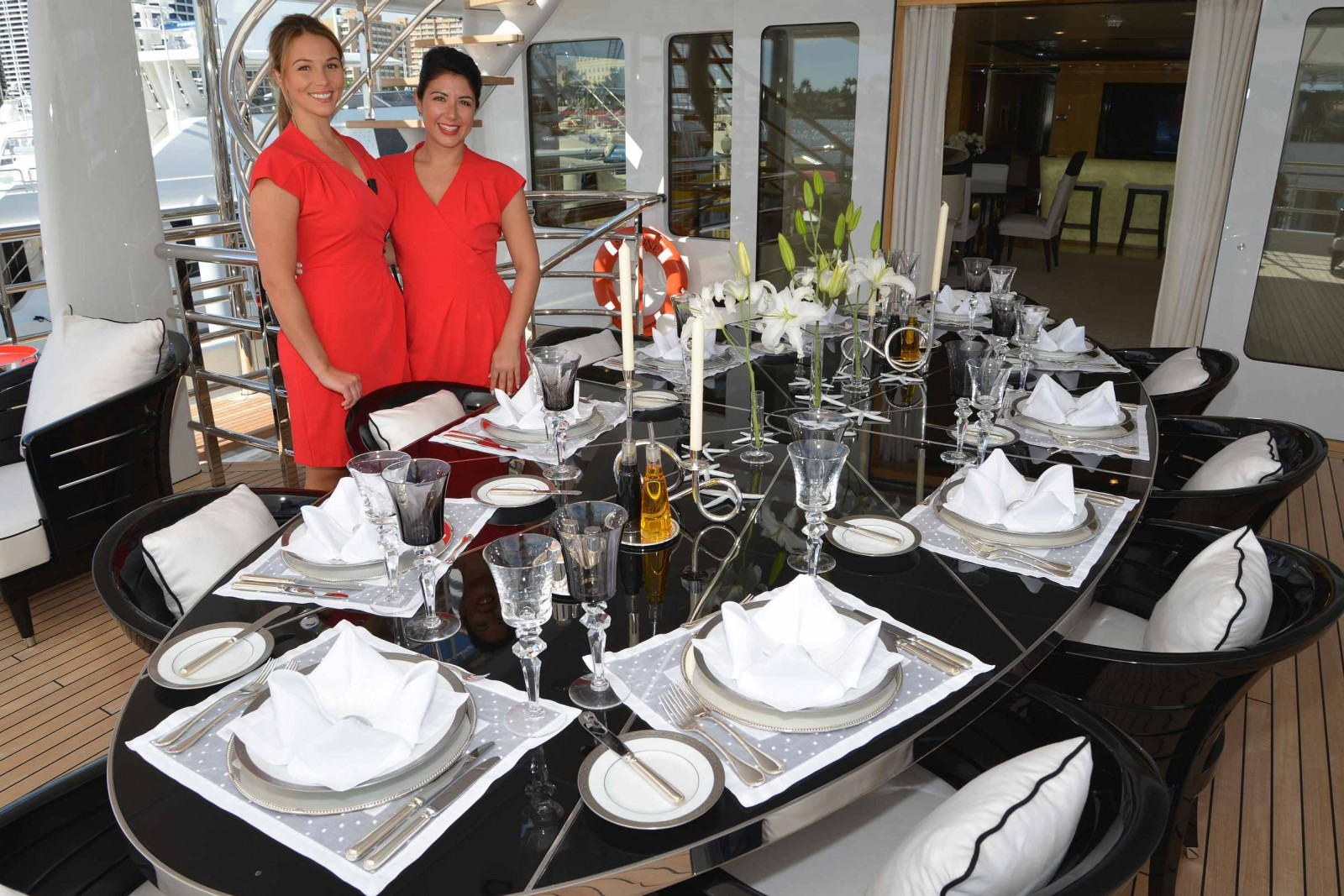 Chief Stew Dani Thompson, left, and Second Stew Chanel Marais of the 180-foot Amels M/Y Step One set two elegant tables for the Top Notch Tabletop competition, which was photographed yesterday for judging on Facebook, which begins after the show. PHOTO/LUCY REED