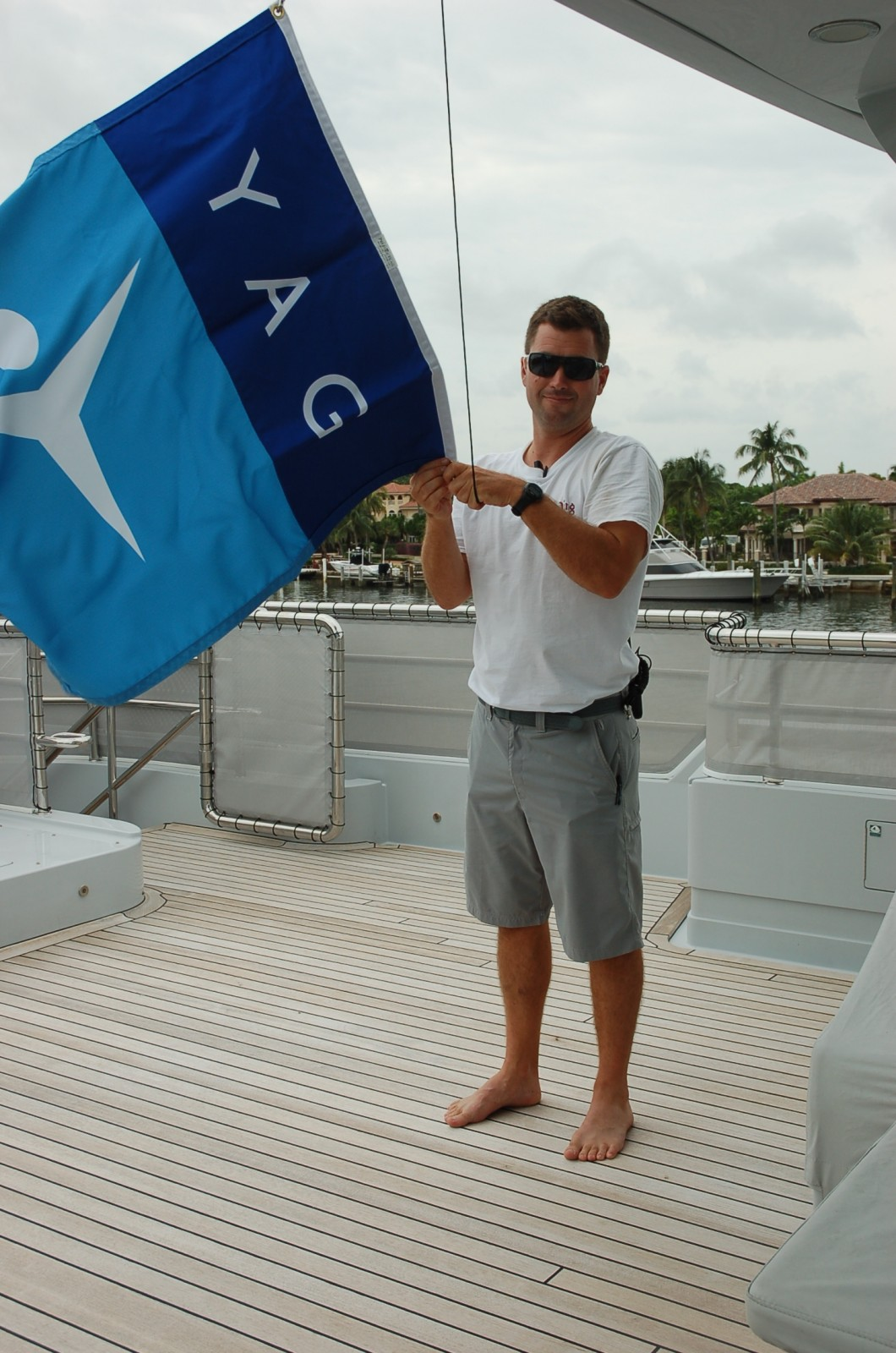 Bosun Mark raises the YachtAid Global flag as the 151-foot M/Y Qing prepares for departure from Bahia Mar in Ft. Lauderdale today. Photo by Lucy Reed