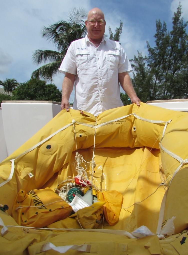 Capt. J.R. Klassen, of M/Y Free Spirit, a 105-foot Northstar, holds the liferaft that held three survivors from a plane crash. PHOTOS/DORIE COX