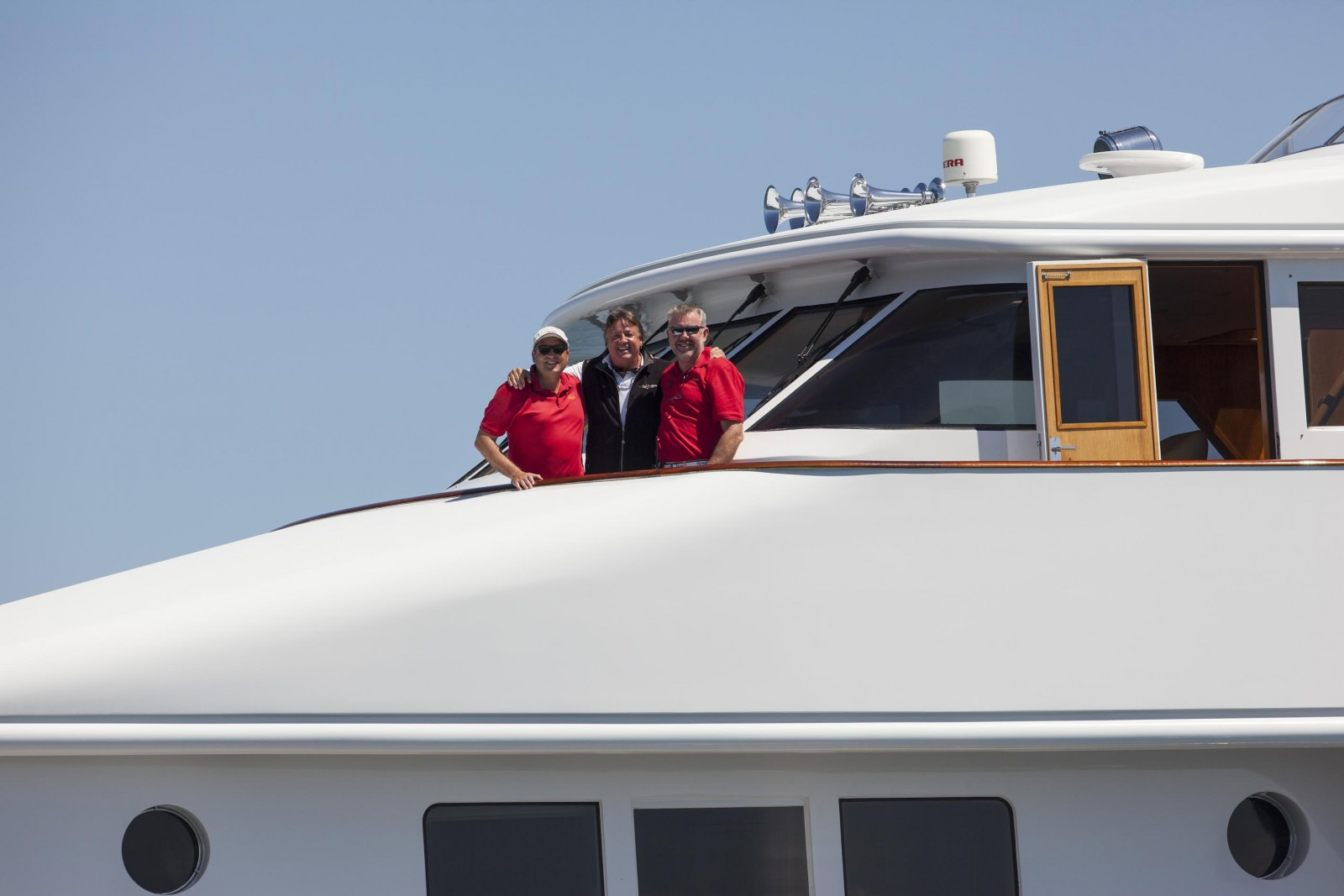 Capt. Ken Bracewell (left) hands over M/Y Rena to the yacht's new master, Capt. Harry Molenaar in Newport, RI in June of 2014. David Lacz (center) brokered the deal. The yacht escorted the whaling ship Charles W. Morgan from Mystic to Newport, Connecticut on the maiden voyage after re-launch. PHOTO BY BILLY BLACK