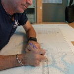 British Admiralty chart annotator Francisco Sheuat hand-corrects a nautical chart to add an AIS symbol onto an aid to navigation. PHOTO BY DORIE COX