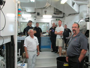Bosun Max Haynes (right, white shirt) shows the engine room on M/Y Archimedes to Newport Rhode Island firefighters, Carl Lessard, yacht loss prevention specialist with AIG (left, white shirt) and Tom Jones, retired U.S. Navy firefighter and head instructor (front right). PHOTOS FROM AIG PRIVATE CLIENT GROUP